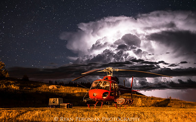 I don't often post photos related to my work fighting forest fires, but I had to share one from this summer.  Late in the evening our helicopter was parked on the helipad outside the office as a violent thunderstorm passed over the park.  Thunder boomed and echoed between the mountains and lightning lit up the sky.  As the storm passed over, the sky cleared and the lightning was replaced with brilliant stars.  Far off in the distance the thunder cell continued to be illuminated by lightning within its midst, and I was able to capture this image.  All the while I wondered if the storm had ignited a fire for us to find the following day…