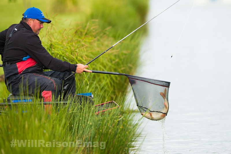 Will Raison lifts a barbel in the landing net, caught with a pole rig in a silver painted top kit.