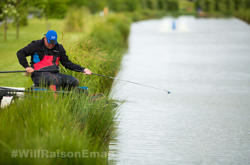 Will Raison plays a hard fighting barbel hooked in the nearside margin beside the pond grass.
