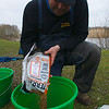 Will Raison pouring a bag of Sensas Terre De Somme into a groundbait mixing bucket. © 2009 Brian Gay