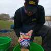 Will Raison pouring a bag of Sensas Migic into a groundbait mixing bucket.