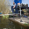 Angler Will Raison plumbing the depth in the near margins to check the clarity of the water. Middle Lake Gold Valley, Aldershot, England. © 2009 Brian Gay