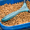 Close-up of 4 mm feed pellets in a bait box with the handle of a PI catty resting on top.