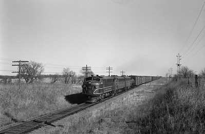 2013.010.CRIP.D.0099--bill kuba 6x9 neg--CRI&P--EMD diesel locomotive 99 on westbound freight train 99 action--west of Palo IA--1963 0322