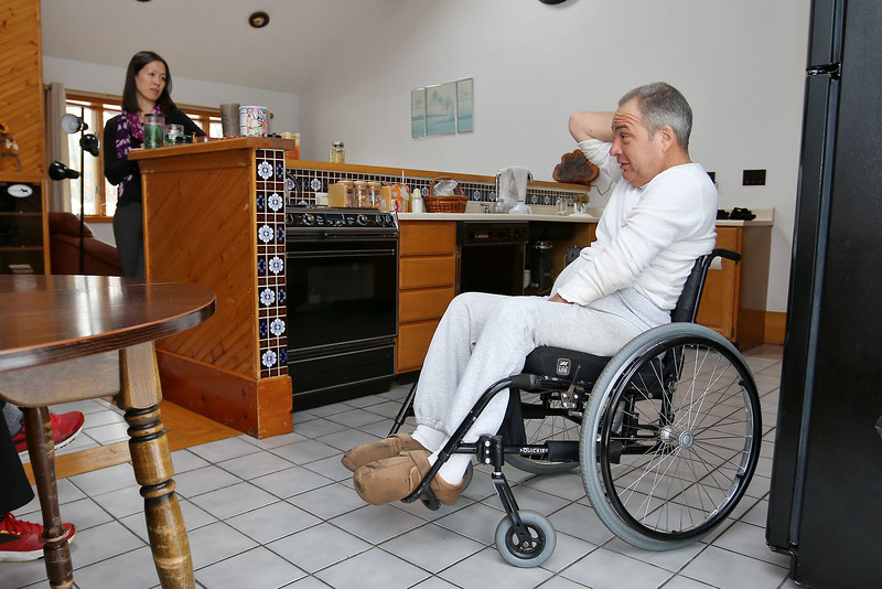 Dr. Ann Hwang, with Commonweath Care Alliance, Inc., listens to William Stimpson, 58, at his home in Billerica on Wednesday February 8, 2017. He gets monthly visits from Commonweath Care Alliance, Inc. which helps him because he is in a wheelchair. SUN/JOHN LOVE