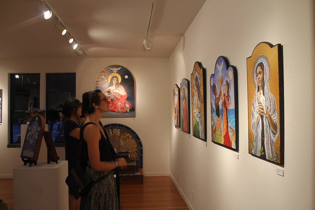 """. Art lovers gaze at works on display during the \""""In the Realm of Spirit\"""" opening Friday, Aug. 4."""