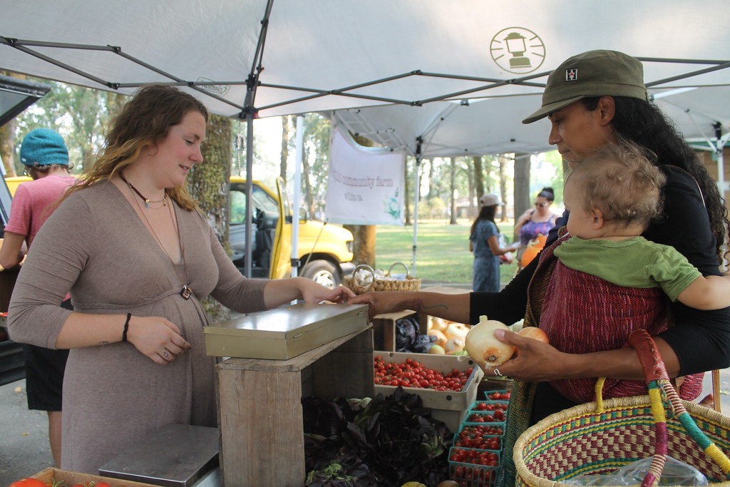 . HILLARY OJEDA/THE WILLITS NEWS Caroline Rehberger of The School of Adaptive Agriculture helping a customer at the Willits Farmers Market on Thursday.