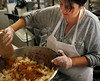 HOLLY PELCZYNSKI - BENNINGTON BANNER Mary Ellen Devlin mixes hand cut apples with cinnamon, sugar and other spices before filling them in delicious pies at Willy's Variety Store & Bakery on Wednesday morning in Bennington. Mary Ellen started the baking pies for Willy's eighteen years ago and has become a Thanksgiving tradition. This year she has baked over 150 pies for customers.