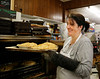 HOLLY PELCZYNSKI - BENNINGTON BANNER Mary Ellen Devlin pulls out fresh baked apple pies at Willy's Variety Store & Bakery on Wednesday morning in Bennington. Mary Ellen started the baking pies for Willy's eighteen years ago and has become a Thanksgiving tradition. This year she has baked over 150 pies for customers.