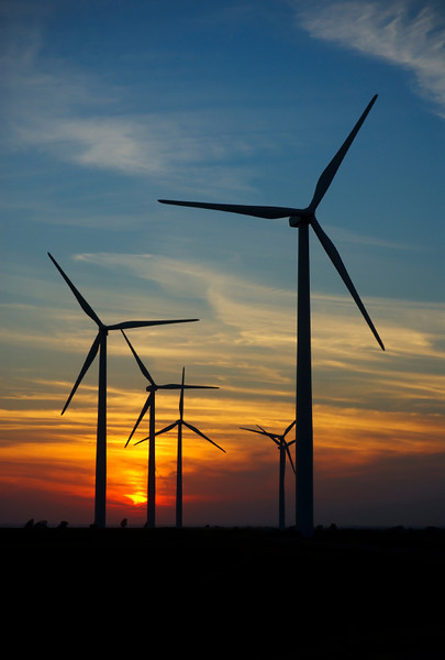The sun sets behind wind turbines generating electrical power.