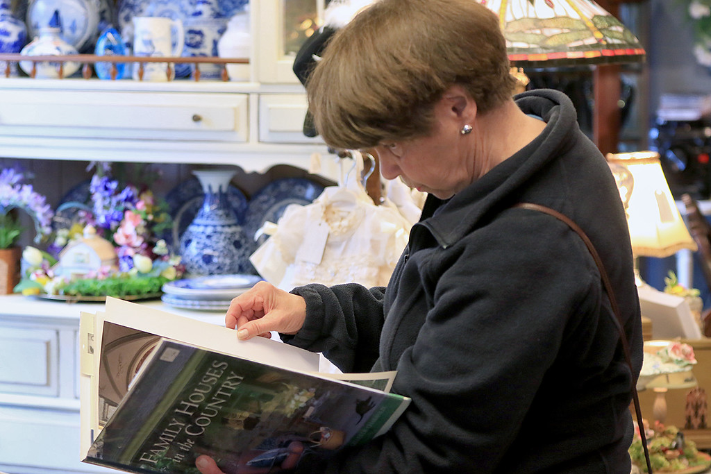 . Windmill Florist & Gifts in Ashby, March 29, 2019. Dottie Houck from Maynard looks through a book for sale in the shop. SENTINEL & ENTERPRISE/JOHN LOVE