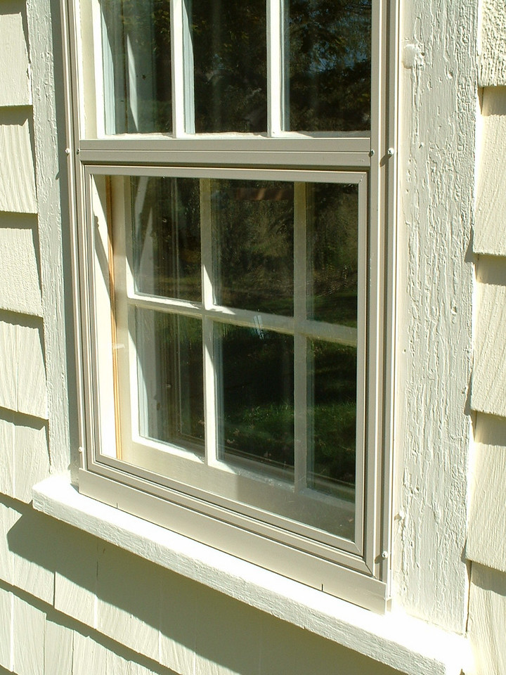 The bottom panel removes to the interior, where it can be replaced with a framed screen.  Both the removable screen and glass panels are held into the storm window frame by clips.