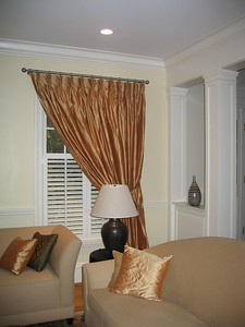 Silk drapery panels mounted on solid brass rods in formal living room