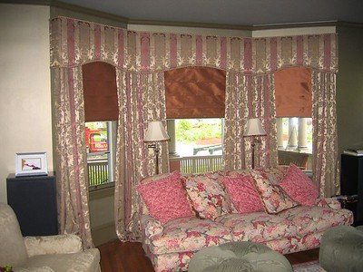 Silk Roman Shades under drapery panels and custom upholstered cornice