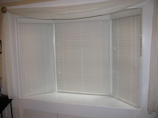 "1 3/8"" Country Wood Blinds in bay window, tilted closed"