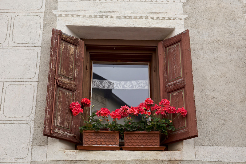 Sometimes bright geraniums are a striking contrast to the the worn wood or chipped paint of the shutters.