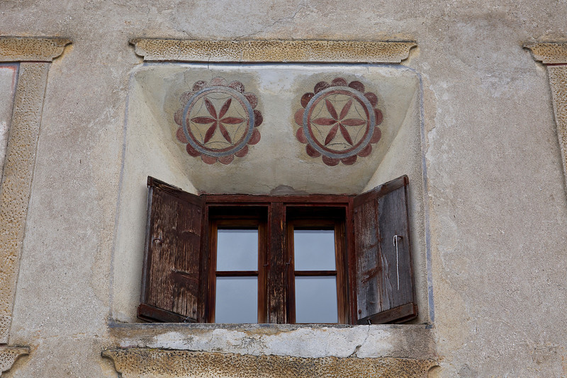 Wall paintings above recessed windows with shutters that are scorched by the sun and frozen by winter winds.