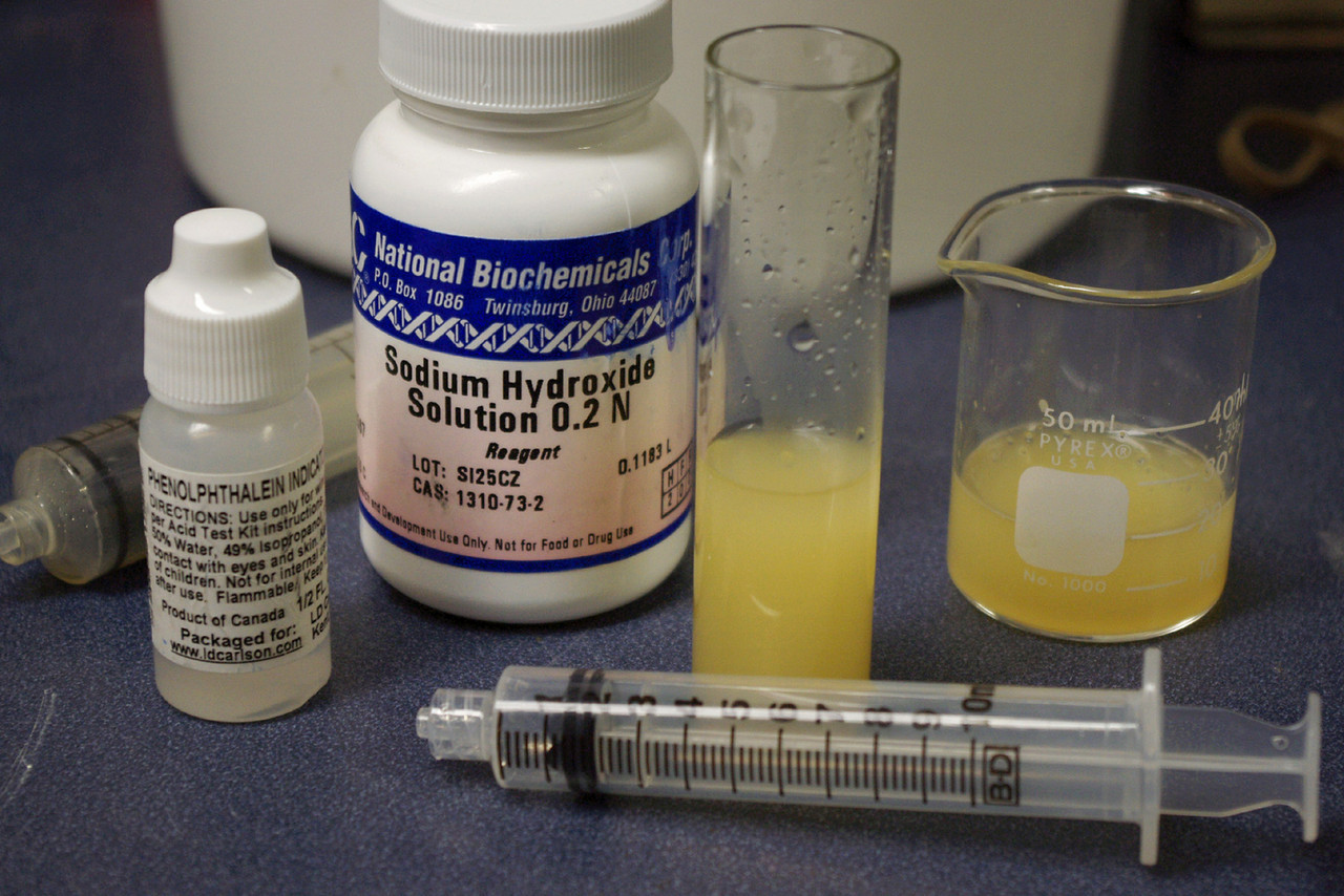 """Traditional acid-base titration reagents.<br /> <br /> A measured amount of wine or  juice and a few drops of phenolphthalein indicator are added to the test vial. The 10 mL syringe is used to slowly add the sodium hydroxide (NaOH) until a pink color is seen. <br /> <br /> The color change indicates the """"endpoint"""" of the titration - and the volume of NaOH required to reach the endpoint is used to calculate the total acidity (TA).<br /> <br /> The exact amount of juice and reagents varies with different kits - they don't all use the same strength of NaOH."""
