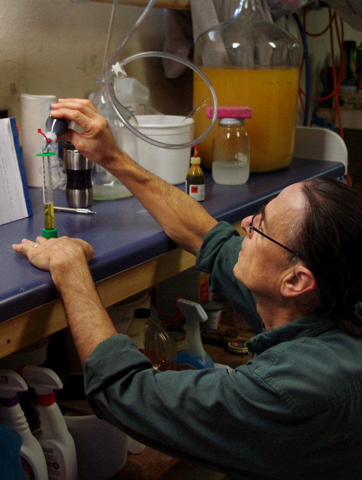 """10/22/10 continued<br /> <br /> Checking the acidity of apple wine using the Vinoferm kit. I've propped up a piece of notebook paper behind the reaction vial to make it easier to see the color in my poorly-lit basement """"lab""""."""