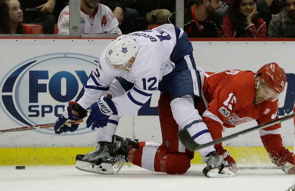 . Toronto Maple Leafs right wing Connor Brown (12) and Detroit Red Wings center Riley Sheahan (15) vie for the puck during the third period of an NHL hockey game, Saturday, April 1, 2017, in Detroit. (AP Photo/Carlos Osorio)