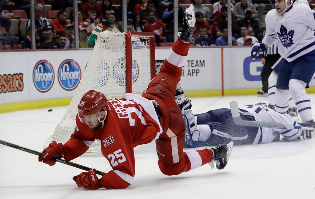 . Detroit Red Wings defenseman Mike Green (25) trips over Toronto Maple Leafs goalie Frederik Andersen (31) during the second period of an NHL hockey game, Saturday, April 1, 2017, in Detroit. (AP Photo/Carlos Osorio)