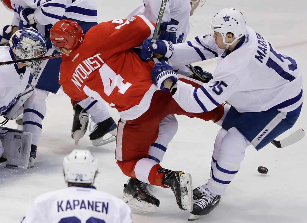 . Toronto Maple Leafs left wing Matt Martin (15) pushes Detroit Red Wings right wing Gustav Nyquist (14) during the first period of an NHL hockey game, Saturday, April 1, 2017, in Detroit. (AP Photo/Carlos Osorio)