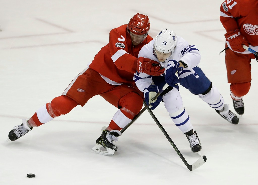 . Detroit Red Wings defenseman Nick Jensen (3) and Toronto Maple Leafs center William Nylander (29) reach for the puck during the first period of an NHL hockey game, Saturday, April 1, 2017, in Detroit. (AP Photo/Carlos Osorio)