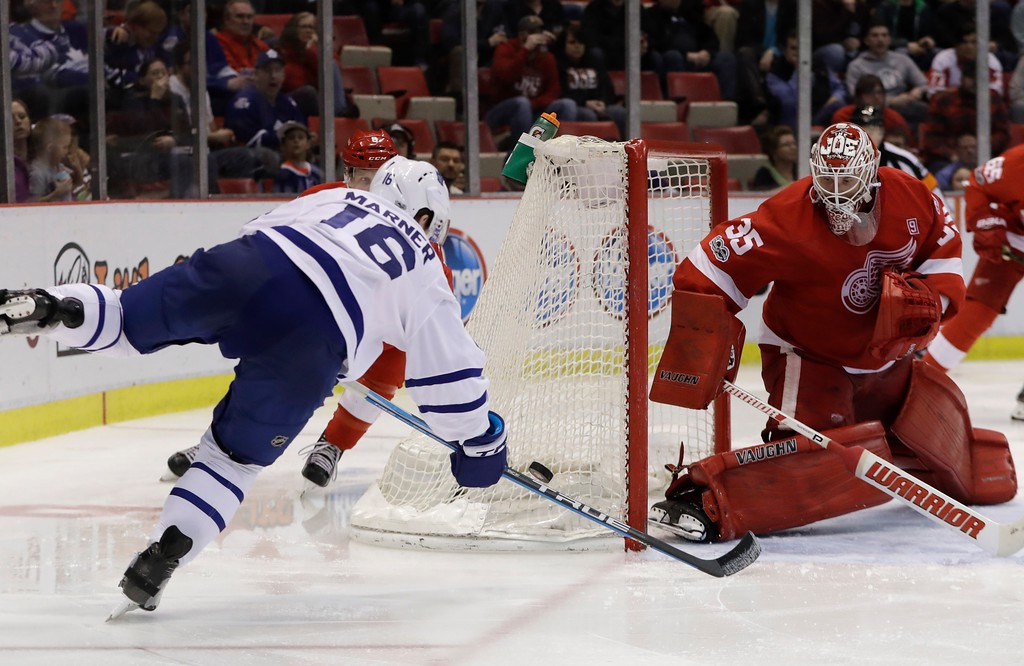 . Toronto Maple Leafs center Mitchell Marner (16) reaches for the puck near Detroit Red Wings goalie Jimmy Howard during the third period of an NHL hockey game, Saturday, April 1, 2017, in Detroit. (AP Photo/Carlos Osorio)