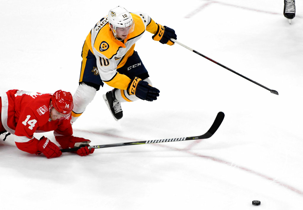 . Nashville Predators center Colton Sissons (10) chases the puck past Detroit Red Wings right wing Gustav Nyquist (14), of Sweden, during the third period of an NHL hockey game Tuesday, Feb. 20, 2018, in Detroit. The Predators won 3-2. (AP Photo/Jose Juarez)