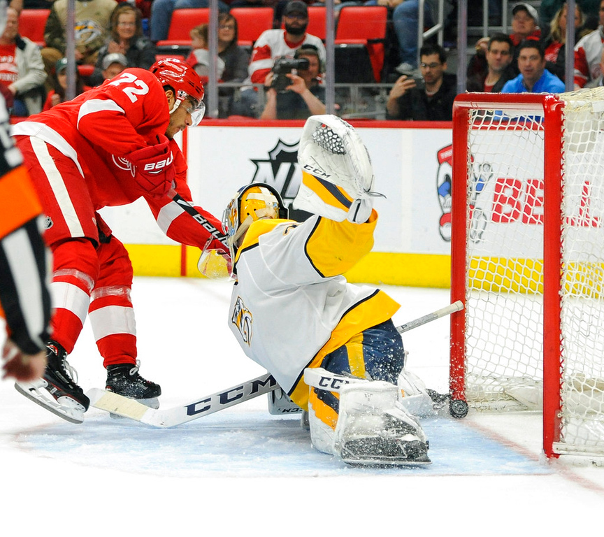 . Detroit Red Wings left wing Andreas Athanasiou (72) scores on Nashville Predators goaltender Juuse Saros (74) in the second period of an NHL hockey game, Tuesday, Feb. 20, 2018, in Detroit. (AP Photo/Jose Juarez)