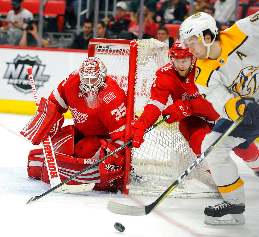 . Nashville Predators left wing Filip Forsberg (9) skates with the puck as he is watched by Detroit Red Wings goaltender Jimmy Howard (35) and defenseman Nick Jensen (3) during the third period of an NHL hockey game Tuesday, Feb. 20, 2018, in Detroit. The Predators won 3-2. (AP Photo/Jose Juarez)