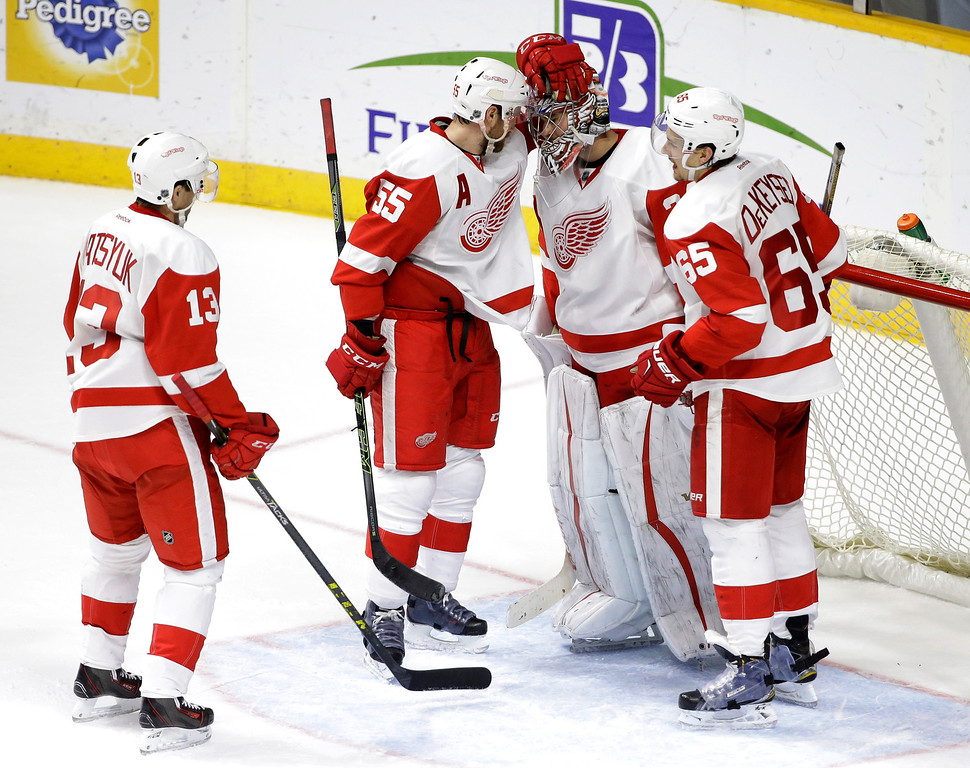 . Detroit Red Wings goalie Petr Mrazek, of the Czech Republic, is congratulated by Pavel Datsyuk (13), of Russia; Niklas Kronwall (55), of Sweden; and Danny DeKeyser (65) after the Red Wings defeated the Nashville Predators 3-2 in an NHL hockey game Saturday, Dec. 26, 2015, in Nashville, Tenn. (AP Photo/Mark Humphrey)