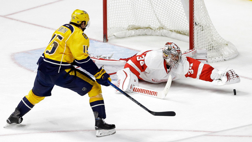 . Detroit Red Wings goalie Petr Mrazek (34), of the Czech Republic, reaches for the puck as Nashville Predators center Craig Smith (15) closes in during the third period of an NHL hockey game Saturday, Dec. 26, 2015, in Nashville, Tenn. The Red Wings won 3-2. (AP Photo/Mark Humphrey)