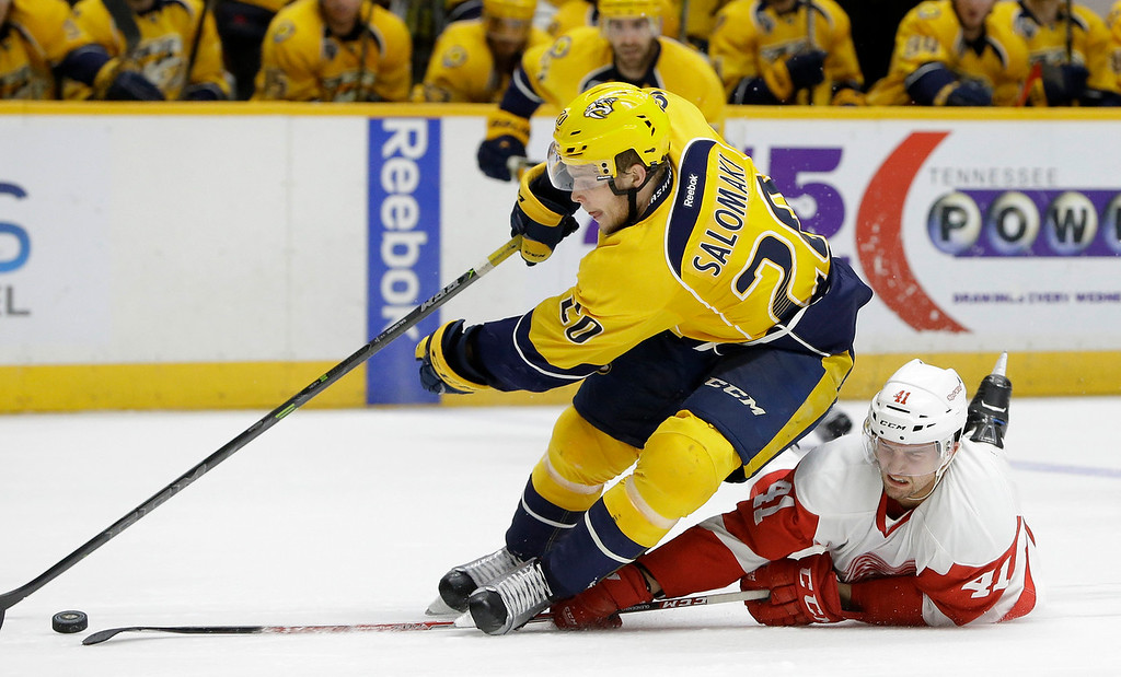 . Detroit Red Wings center Luke Glendening (41) defends Nashville Predators forward Miikka Salomaki (20) during the second period of an NHL hockey game Saturday, Dec. 26, 2015, in Nashville, Tenn. Glendening was called for tripping on the play. (AP Photo/Mark Humphrey)