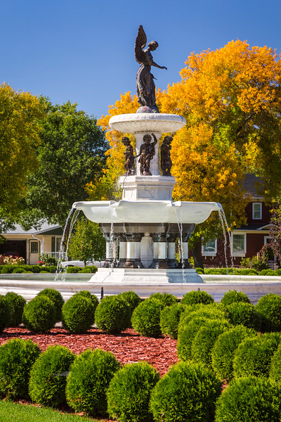 The Angel of the Waters Fountain with fall foliage color in the Bethel Heritage Park in Winkler, Manitoba, Canada.