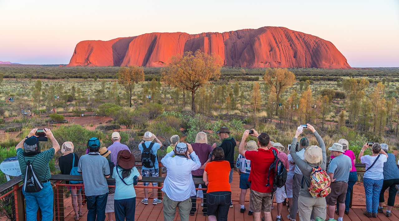 Tourists watch the sunrise at Uluru, formerly known as Ayers Rock, Australia. This photo won Third Place in the March 2016 Travel competition of the Alameda Photographic Society as well as Fourth Place from the Northern California Council of Camera Clubs.