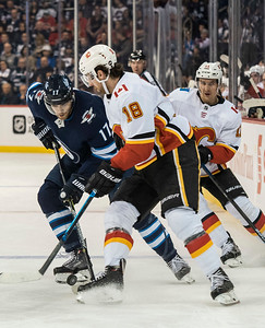 DAVID LIPNOWSKI / WINNIPEG FREE PRESS  Winnipeg Jets #17 Adam Lowry looks to get the puck past Calgary Flames #18 James Neal Thursday December 27, 2018 at Bell MTS Place.