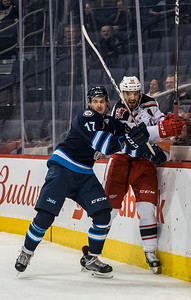 DAVID LIPNOWSKI / WINNIPEG FREE PRESS  Manitoba Moose Jimmy Lodge (#17) checks Grand Rapids Griffins Brian Lashoff (#18) into the boards during second period action at Bell MTS Place Wednesday January 10, 2018.