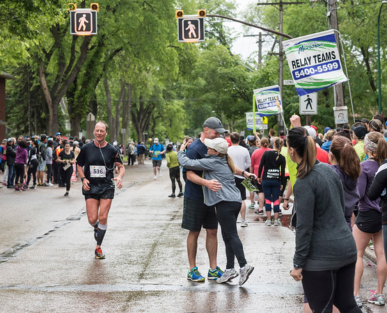 DAVID LIPNOWSKI / WINNIPEG FREE PRESS  Manitoba Marathon relay participants Miles Macdonell gets a hug from National Leasing coworker Alfie Imbrogno as they hand off during their run on Wolseley Avenue Sunday June 18, 2017 in a relay exchange zone.