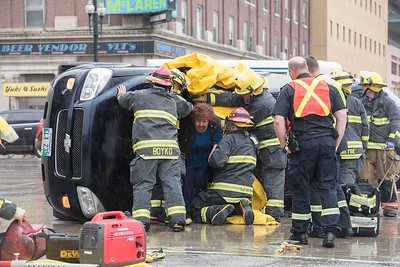 DAVID LIPNOWSKI / WINNIPEG FREE PRESS  Winnipeg Fire and Paramedics help occupants of a turned over van escape through the windshield at the corner of Rupert Ave and Main Street during rush hour traffic Wednesday May 25, 2016.