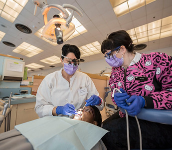 DAVID LIPNOWSKI / WINNIPEG FREE PRESS   Dr. Karina Gamboa (left) and Dr. Carla Cohn (right) work on Mwashite Mbekalo of Tanzania at the University of Manitoba's College of Dentistry Saturday November 5, 2016. The Manitoba Dental Association and the University of Manitoba's College of Dentistry hosted 'OPEN WIDE', a day of free dental services for refugees.