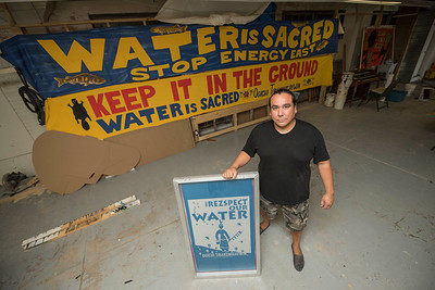 DAVID LIPNOWSKI / WINNIPEG FREE PRESS  Clayton Thomas Muller, the aboriginal environment liaison for 350.0rg and a lead local organizer for the 5,000 mile journey of the totem pole from the Salish Coastal peoples to Treaty One here in Manitoba poses with banners  Saturday September 3, 2016. The art and banners will be used in the procession of the totem pole on Monday.