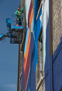 DAVID LIPNOWSKI / WINNIPEG FREE PRESS  Patrick Thompson and Alexa Hatanaka (not pictured) work on one of two large scale murals that are being worked on Main Street as part of a month-long celebration of public art by Synonym Art Consultation Saturday September 3, 2016.