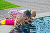 Three children playing in the water in a decorative pool in the English Gardens at the Assiniboine Park in Winnipeg, Manitoba, Canada.