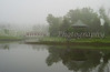 Calm waters on the lake reflect the Chinese pagoda on a misty morning at Kings Park in Fort Garry, Winnipeg, Manitoba, Canada.