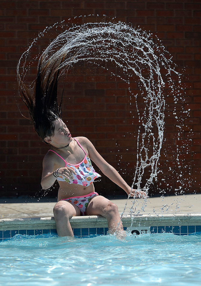 Aspyn Martinez, 11, flips her hair after dipping it in the pool Tuesday, May 30, 2017, at Winona Pool in Loveland. The pool opened on Memorial Day for the summer.  (Photo by Jenny Sparks/Loveland Reporter-Herald)