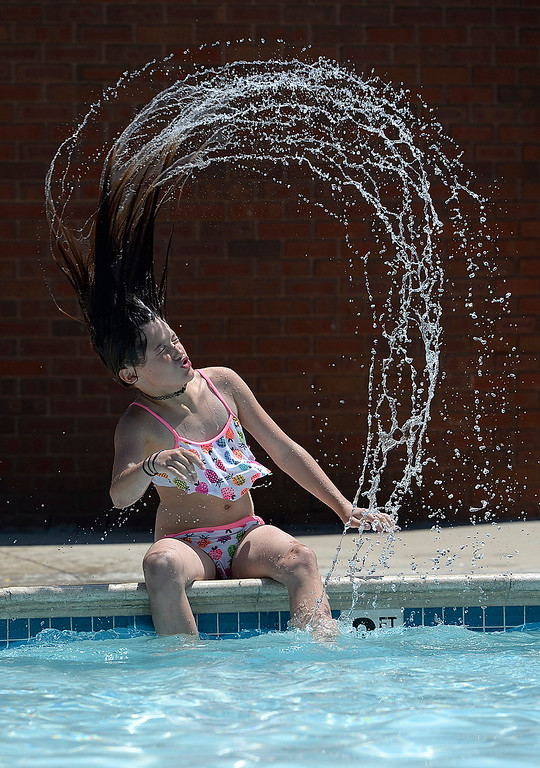 . Aspyn Martinez, 11, flips her hair after dipping it in the pool Tuesday, May 30, 2017, at Winona Pool in Loveland. The pool opened on Memorial Day for the summer.  (Photo by Jenny Sparks/Loveland Reporter-Herald)