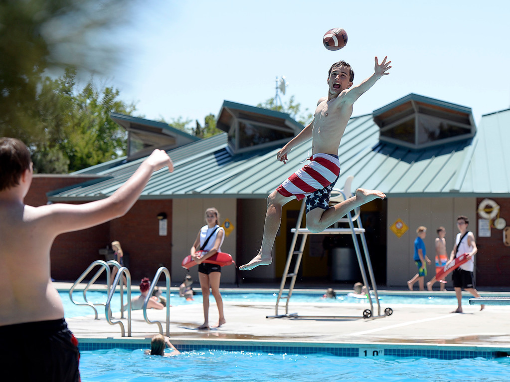 . Jasen Shaffer, 13, tries to catch a football thrown by his pal Matthew Olsen, 14, left, as he jumps off the diving board Tuesday, May 30, 2017, at Winona Pool in Loveland. The pool opened on Memorial Day for the summer.  (Photo by Jenny Sparks/Loveland Reporter-Herald)