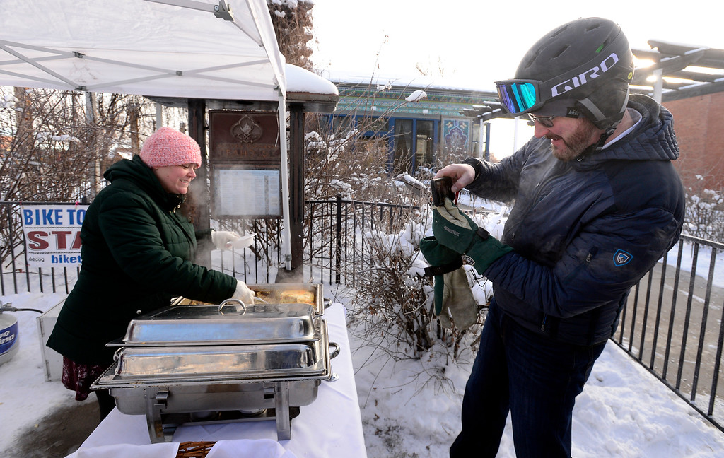 """. BOULDER, CO - FEBRUARY 8, 2019 Dave \""""DK\"""" Kemp takes a photo of the hot breakfast being served by Jill King outside the Boulder Dushanbe Teahouse during Winter Bike to Work Day on Friday February 8 2019.   For more photos go to dailycamera.com (Photo by Paul Aiken/Staff Photographer)"""