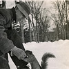Man crouching down in snow to feed squirrel,  ca. 1905?